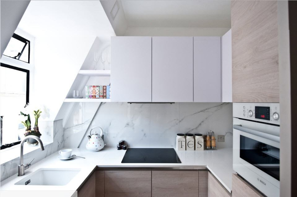 Loft architecture of the small kitchen with matte top tier of cabinets and gray colored lower tier
