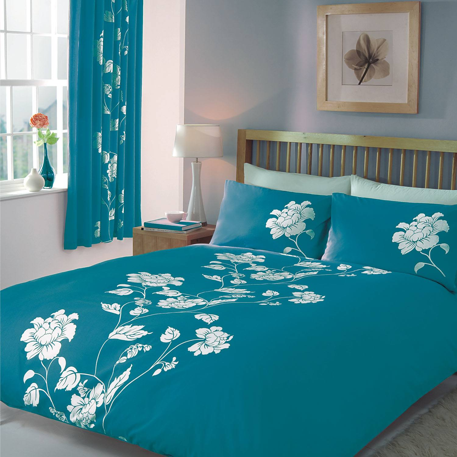 Azure colored bedroom linen with same pattern on the curtains