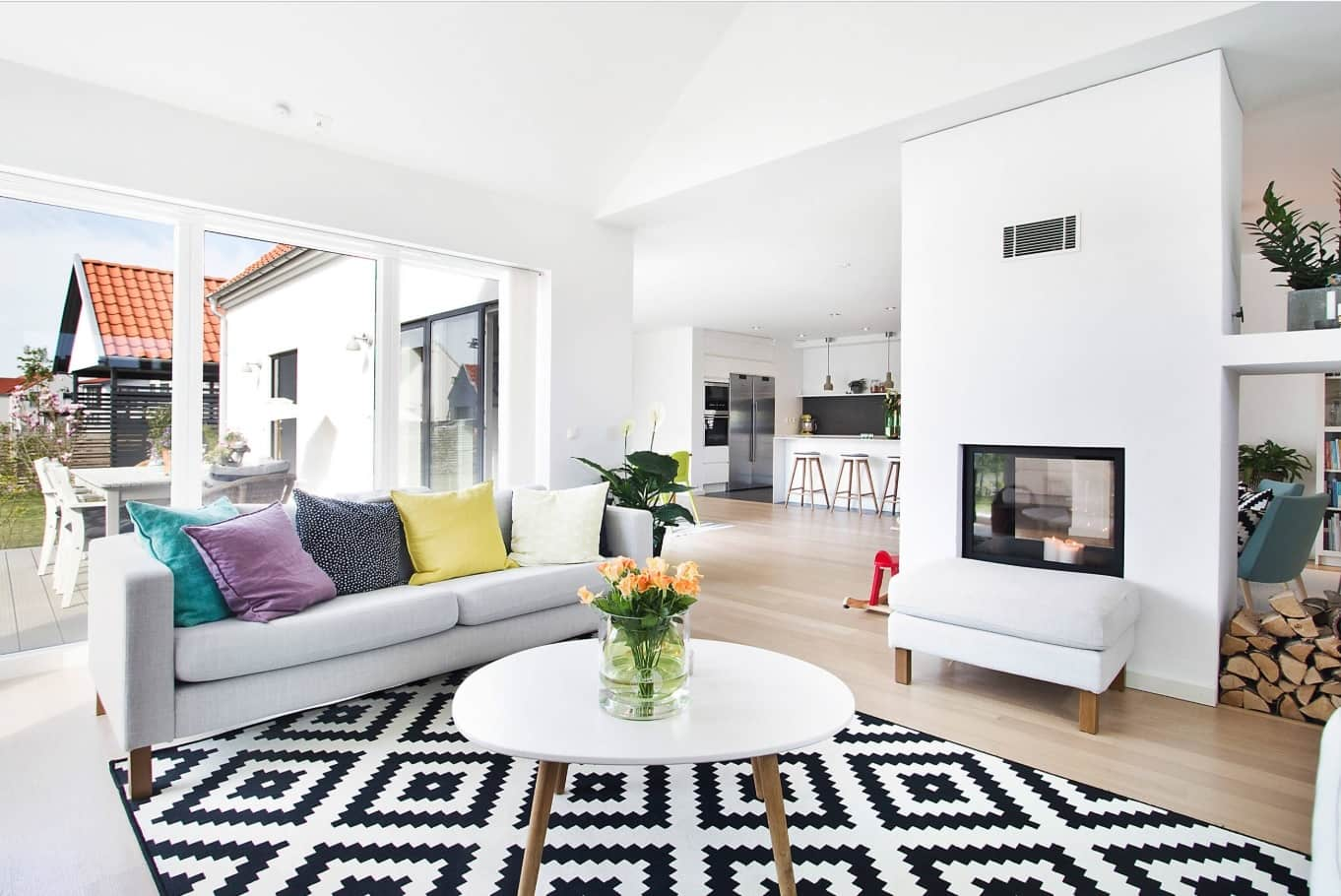 4 Reasons To Add A Fireplace To Your Living Room. white Scandinavian styled room with checkered rug and artificial hearth built into partition wall