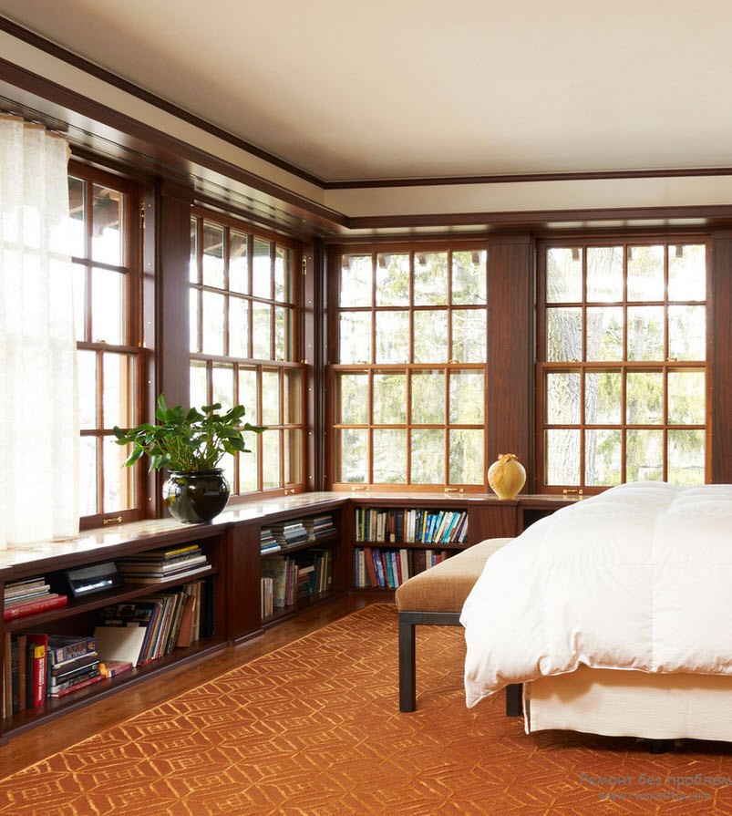 Unusual businesslike interior of the bedroom with wooden casement windows and book shelving at the low level