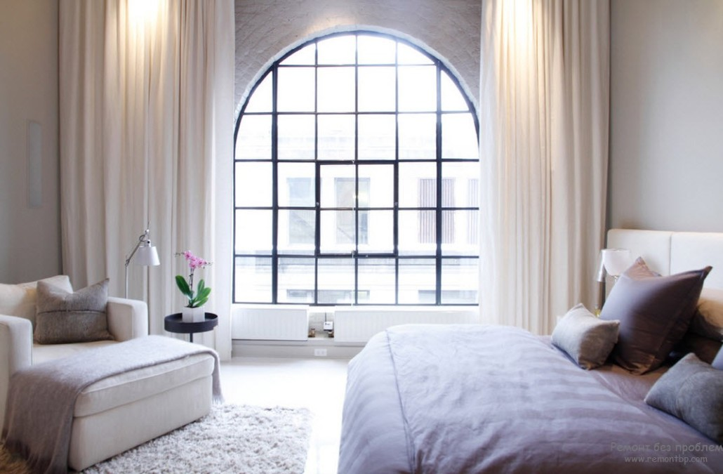 Huge arched sash window for the contemporary styled room with high ceiling and light pastel color scheme