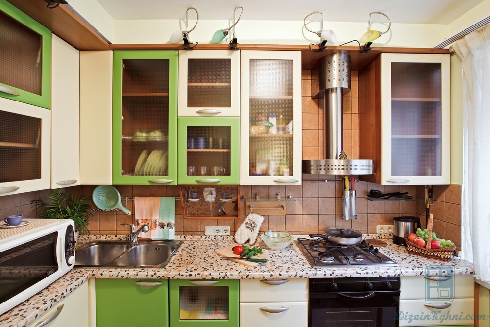 Green facaded simple styled kitchen with the additional light spots and exposed steel extractor hood