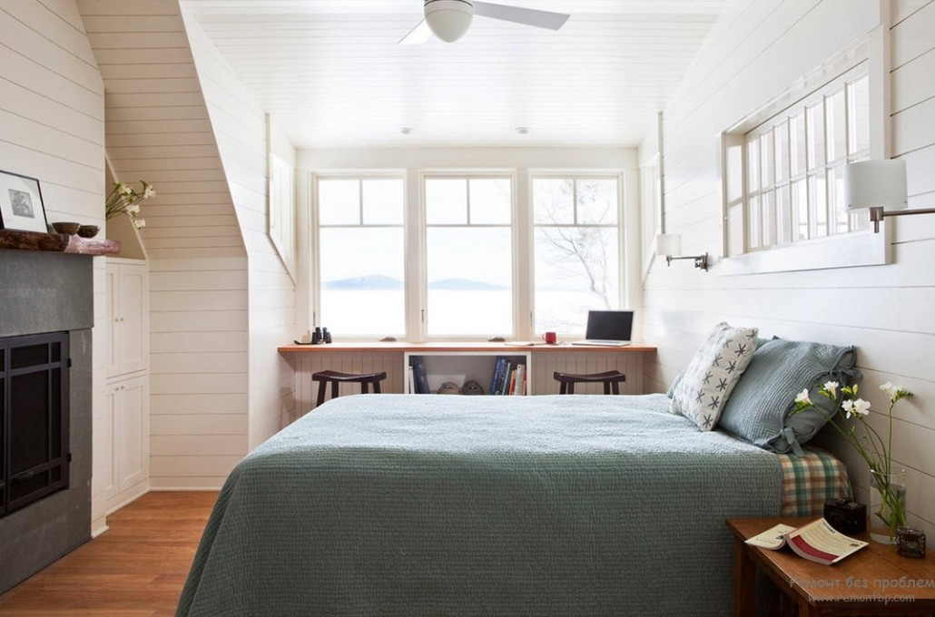 Casual styled white room with large bed and the table ath the window