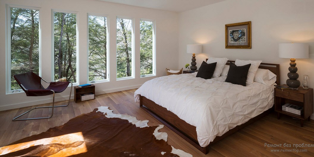 Window Design in the Bedroom for Ultimate Coziness and Comfort. Cow pelt and large bed in white room
