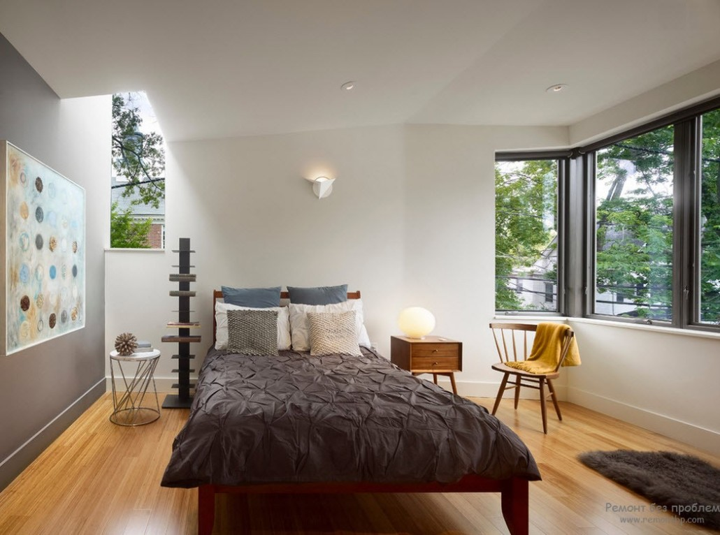 Dark bed in the light creamy colored bedroom with laminated floor