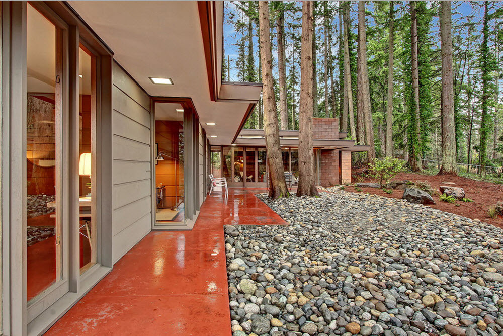 Original Country House Design in Red Color. The backyard decorated with large pebbles