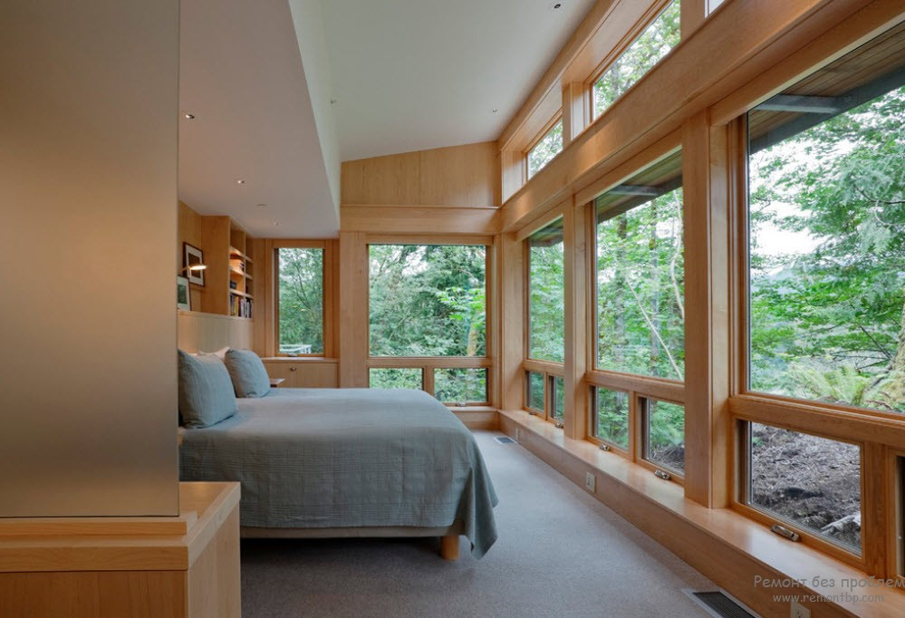 Window Design in the Bedroom for Ultimate Coziness and Comfort. Wooden trimmed private house interior with large windows and contrasting gray bed linen