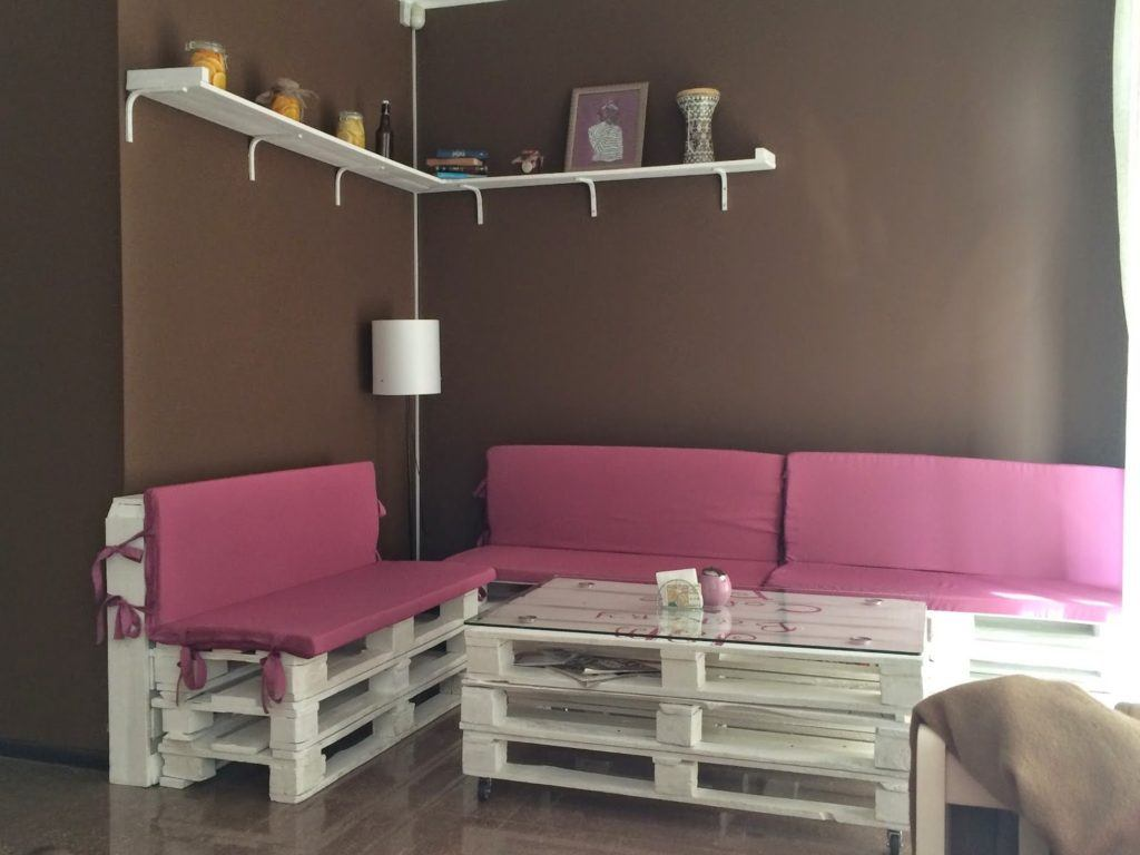 Gorgeous casual interior design with angular sofa made of pallets and same material for the table with glass top