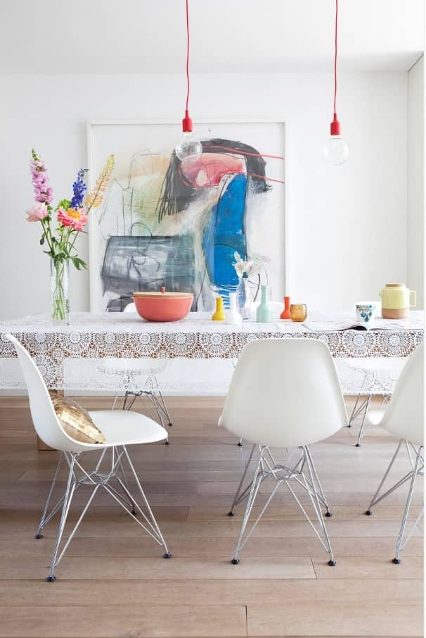 Top Tips for Making Sure Your Home Is Party-Ready. White designed dining room with plastic chairs and flowers on the table