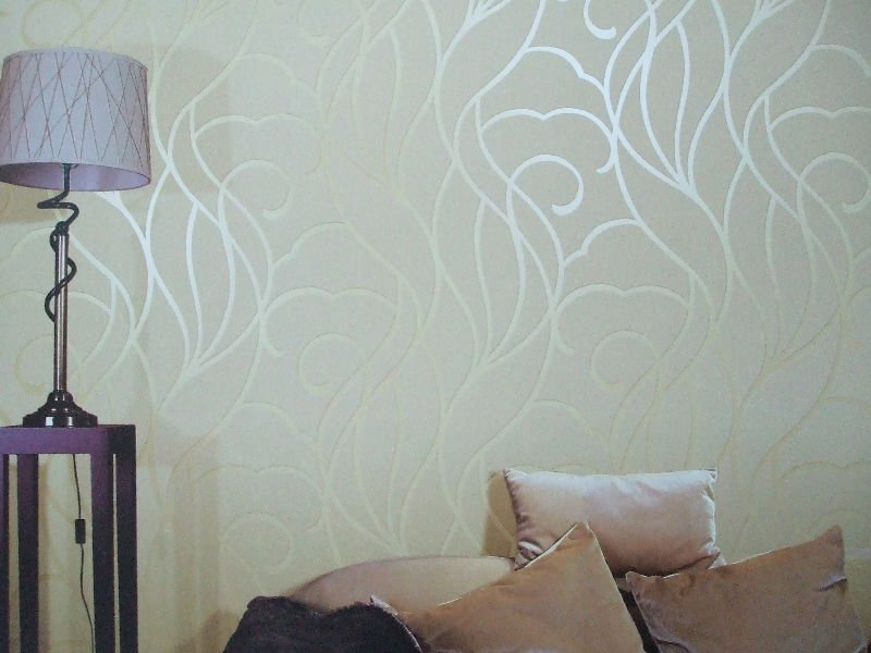 Glossy pattern of the neat pale yellow wallpaper in the bedroom