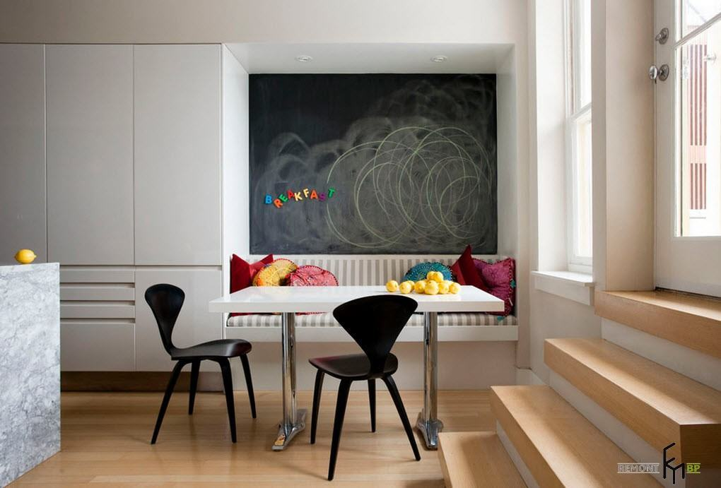 Black chalkboard of the white colored modern kitchen with smooth furniture set