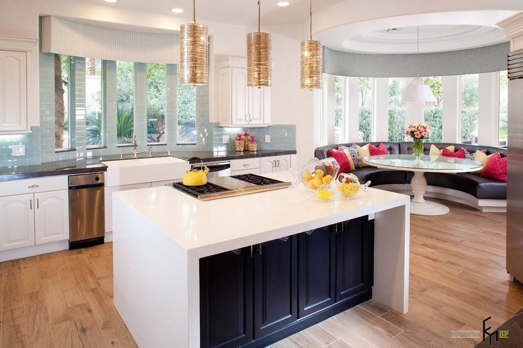 White topped island with black sides and golden pendant lamps over it