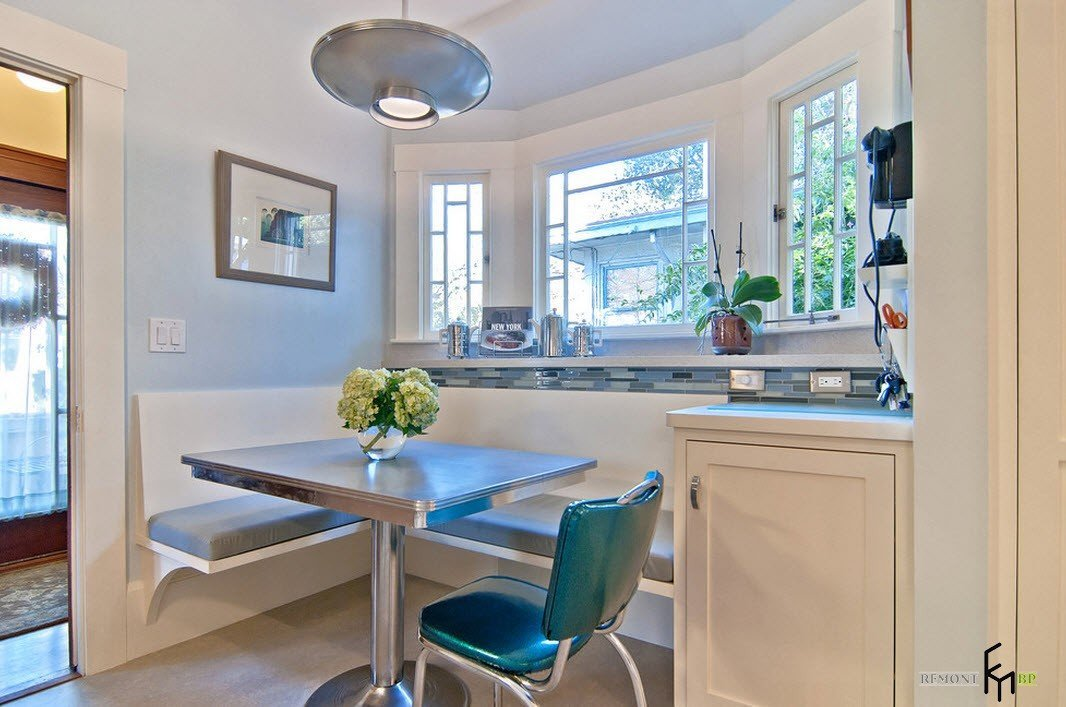 Dining Area with Corner Furniture Set. Large American styled kitchen in white with green chairs and gray bench