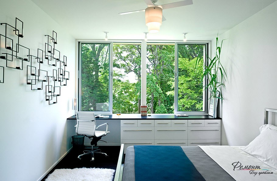 Large window and the storage systems at the windowsill in the modern styled bedroom