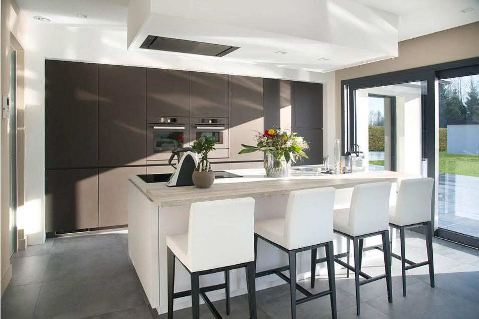 Gray accent wall in the white colored kitchen full of natural light and with creamy white chairs at the dining area