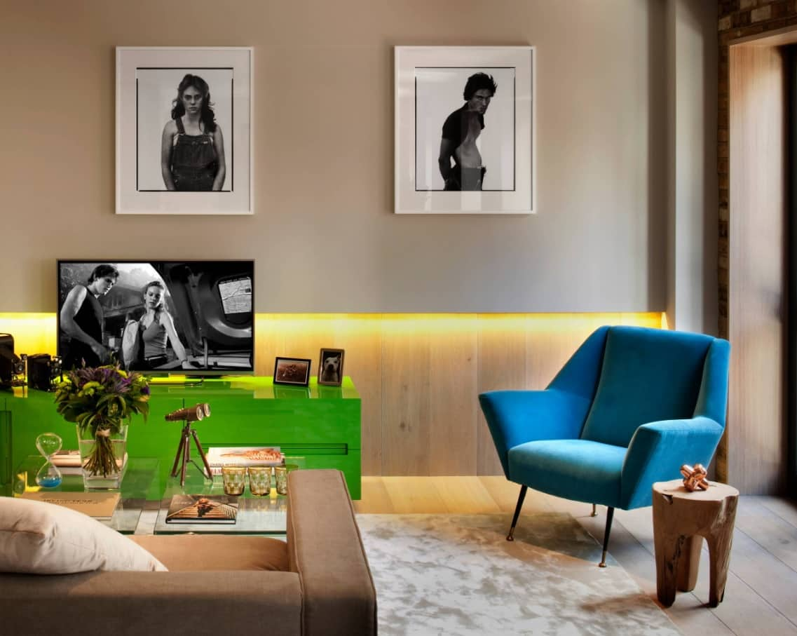 Lighting Tricks to Make a Small Home Feel Larger. Led lighting in the wooden trimmed modern styled living room with blue atmchair and pictures for decoration