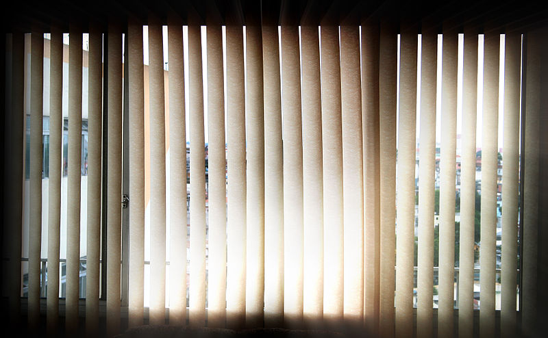 Using Vertical Blinds to Complement Interior Decor. Simple cloth painted curtains at the panoramic window
