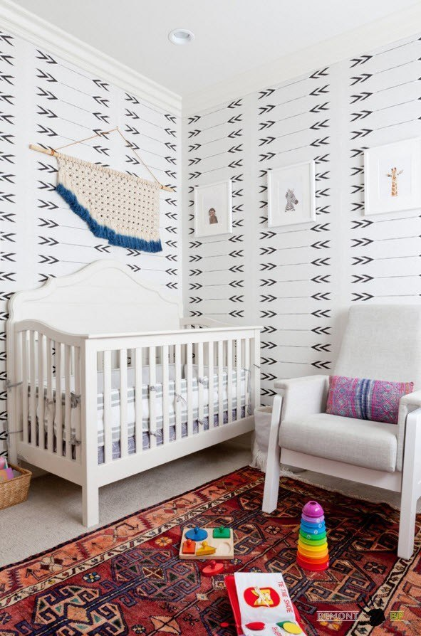 calm light gray design of the room with upholstered armchair and the crib