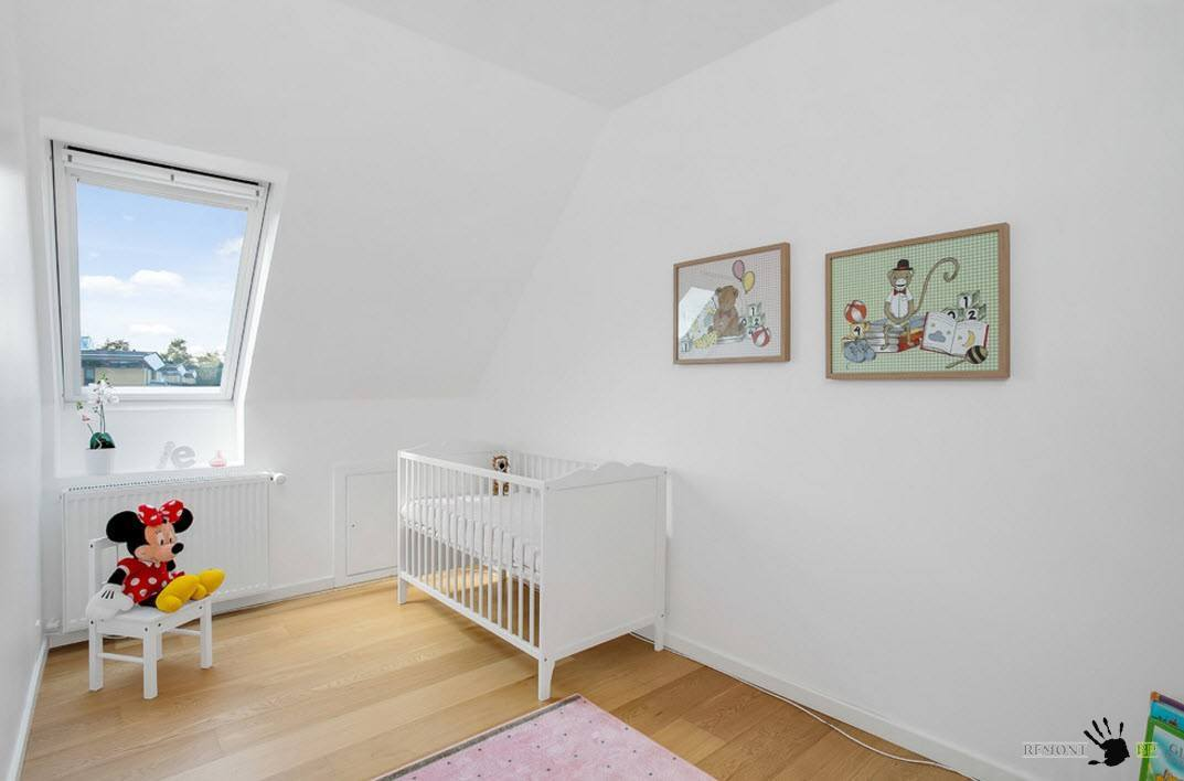 Neat and properly lit nursery with small cot and sloped ceiling