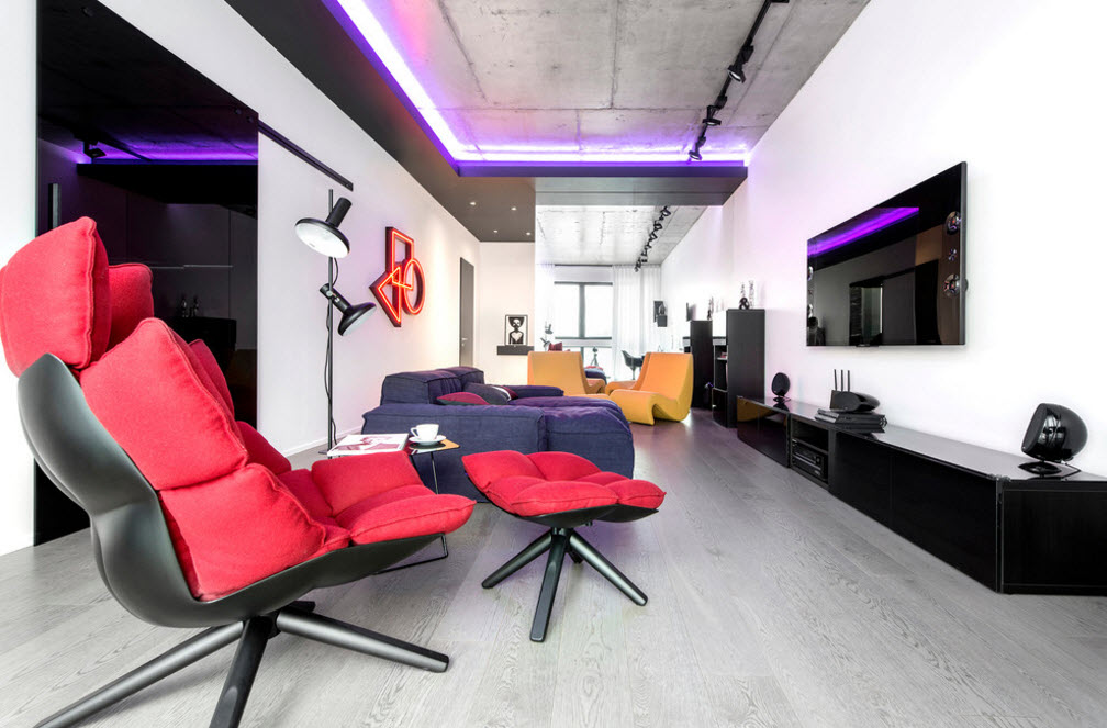 Daring Black and White Home Design Project with Neon Lighting. Red relaxing chair and the dark blue sofa for open space living in minimalistic style