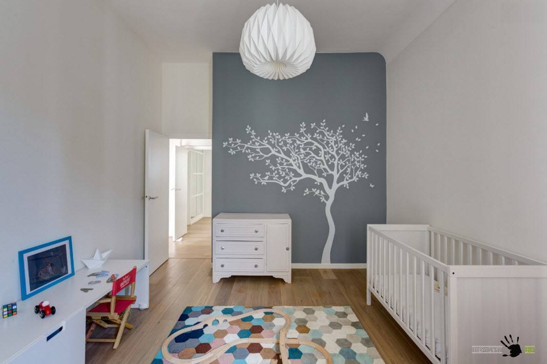 Nursery with painted tree, colorful rug, and white furniture