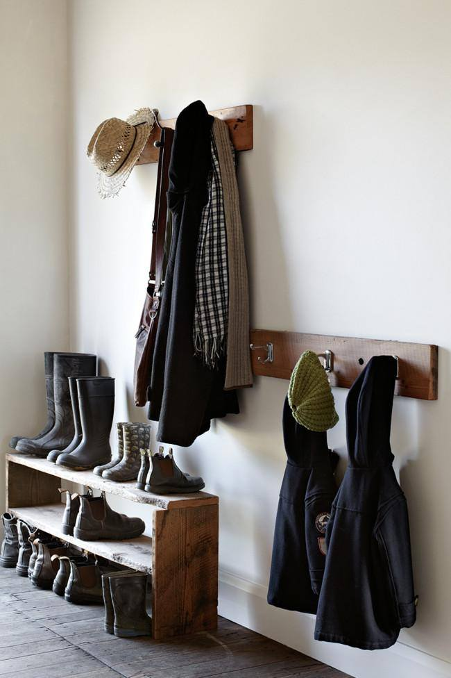 Open wooden shelf for footwear and hanger for clothes at small white corridor