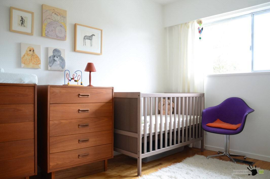 Wooden chest of drawers and the gray crib in the nrusery