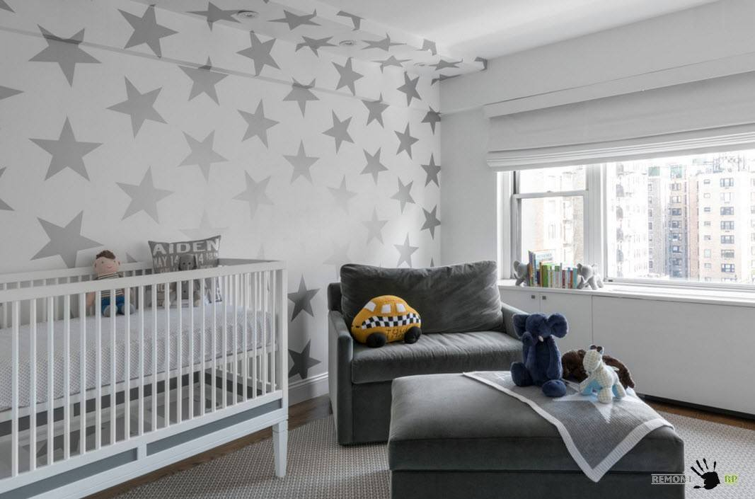 Starry wallpapered interior with small crib for infant