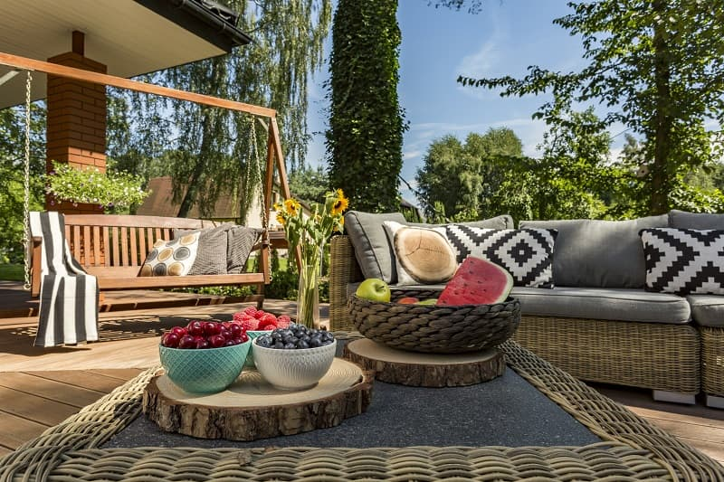 Amazing Reasons Of Having An Outdoor Patio Installed In Summers. Opan-air sitting zone with the wooden swing and DIY wooden vase stands