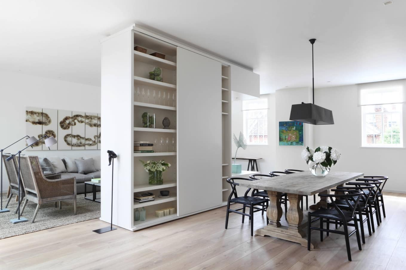 Black Dining Room Set for Different Interior Styles. Dark dining group in the open space apartment with the bookshelf as delimiting partition