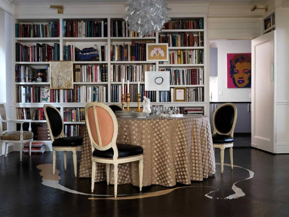 Library and the round tablecloth covered table in the dining room with black floors and chairs