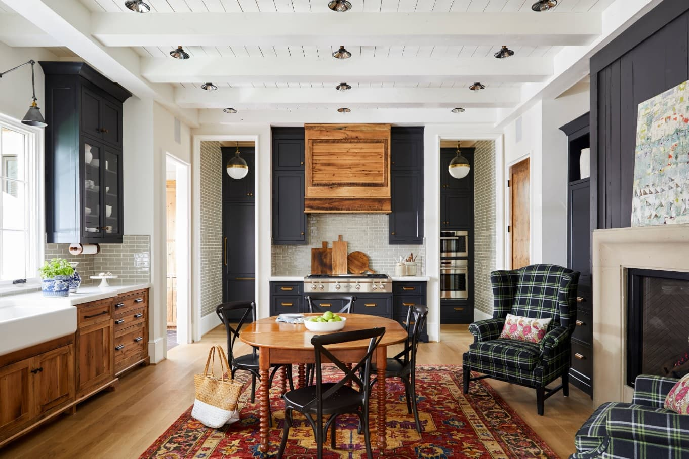 Coffered white ceiling and black inlays for Casual design of the dining room with Persian rug in the center