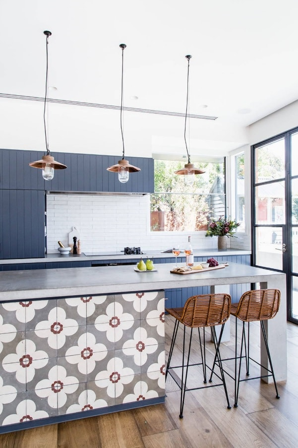 Simple vintage lamps with copper shades over the kitchen island decorated with tiled flowers