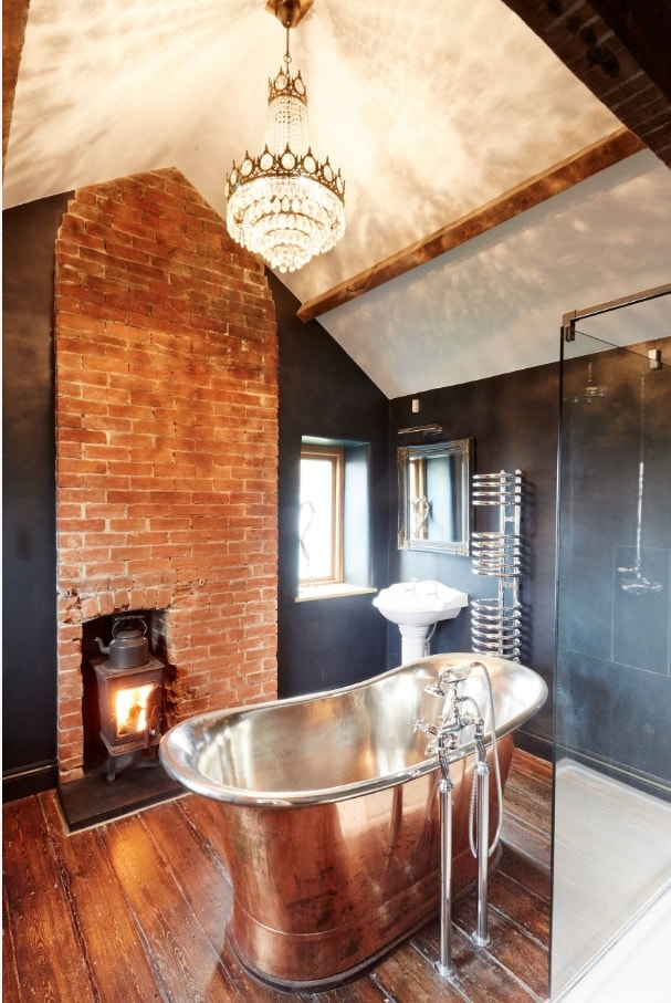 Chic copper oval bathtub as a highlight of vintage bathroom with brickwork