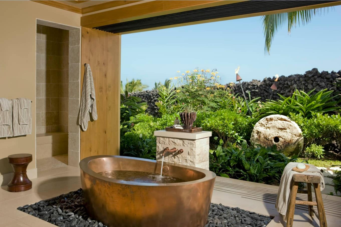 Panoramic glass wall to the backyard of the tropic house with oval copper bathtub in the center lying on pebbles