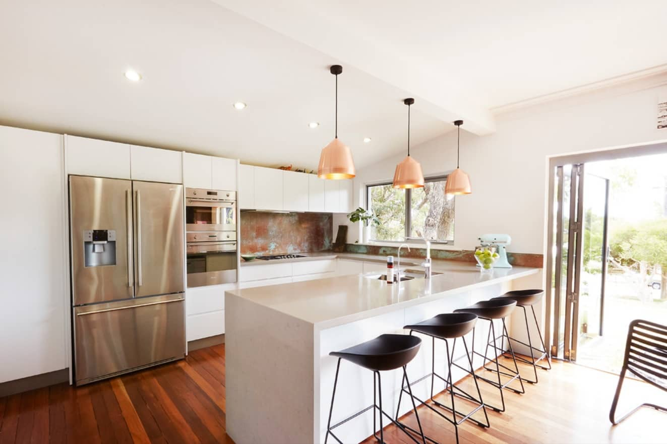 Modern styled light colored kitchen with steel surfaced fridge, natural wooden floor and black seating group at the island