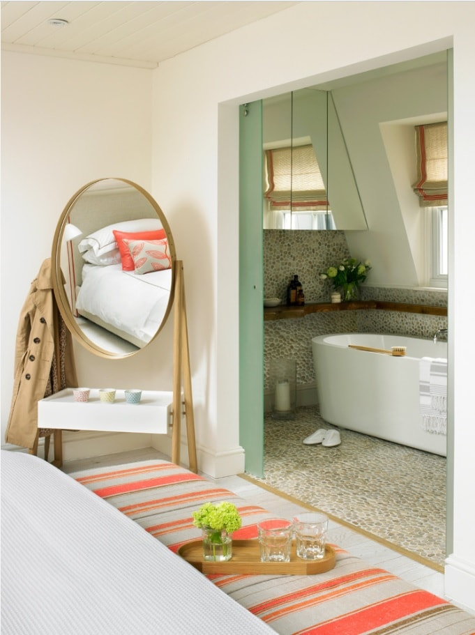 Ensuite Bathroom as the Way to Organize Space. Large oval swivel mirror at the bedroom with open way to bathroom