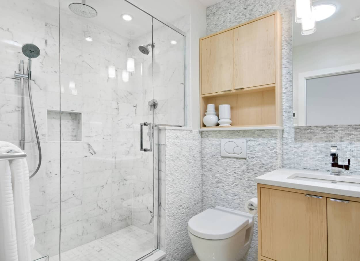 Ensuite Bathroom as the Way to Organize Space. Gray marble trimmed shower zone and wooden furniture