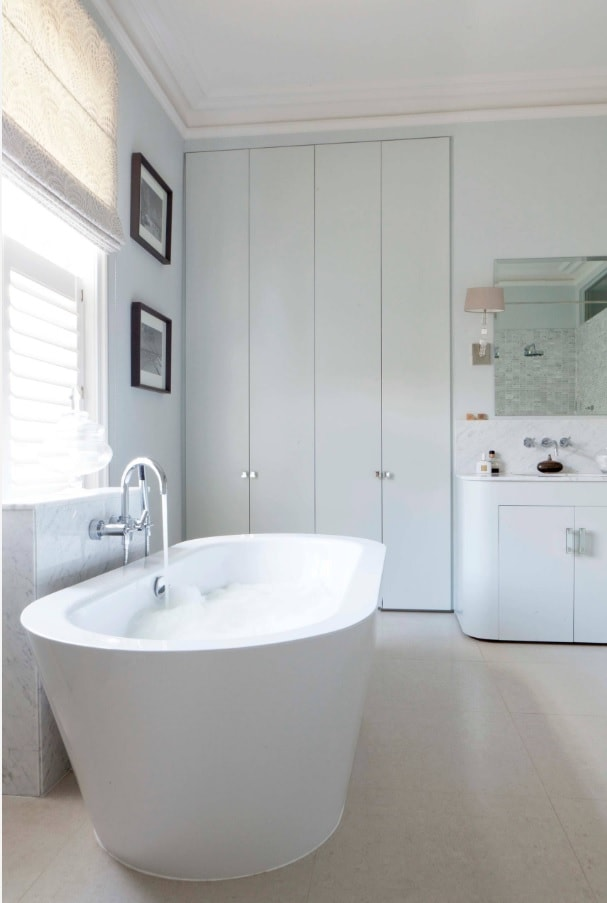 Ensuite Bathroom as the Way to Organize Space. White wall panels and oval artificial stone bathtub