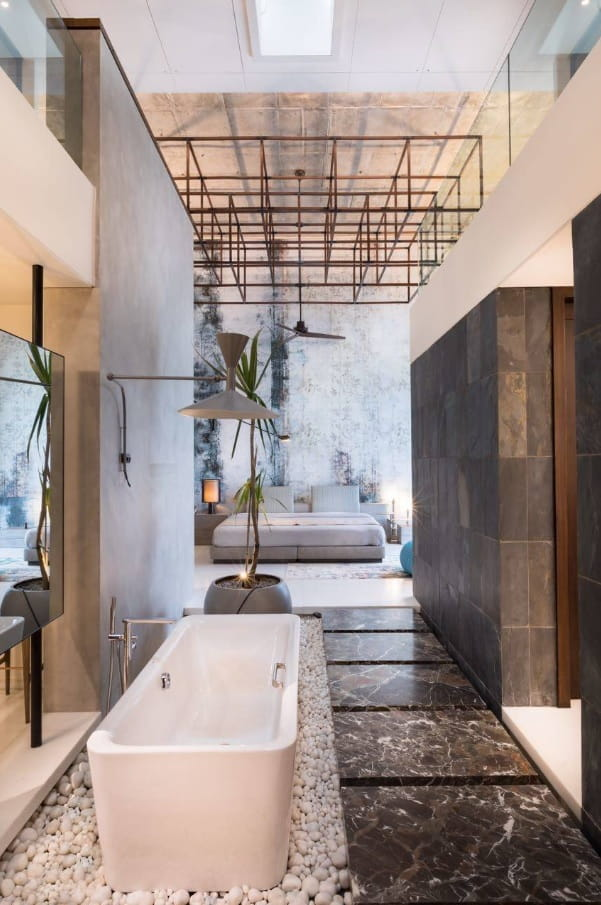 Unexpected metal grid at the ceiling and center located bathtub in contemporary styled bathroom