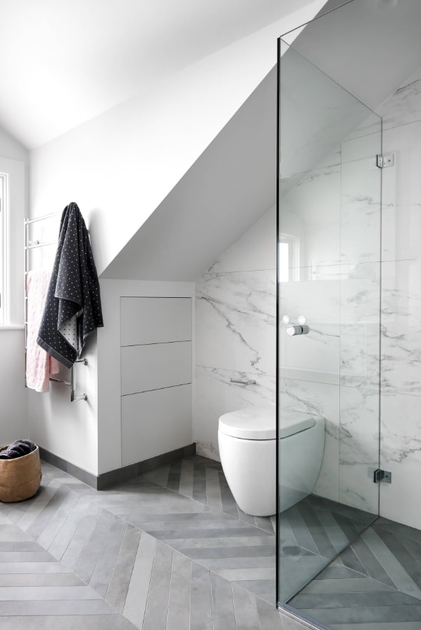 Loft architecture of the bathroom with white wall and marble trimmed shower zone