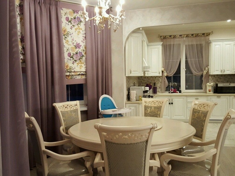 Velvet curtains and round milky colored table with upholstered classic chairs for large kitchen with arch