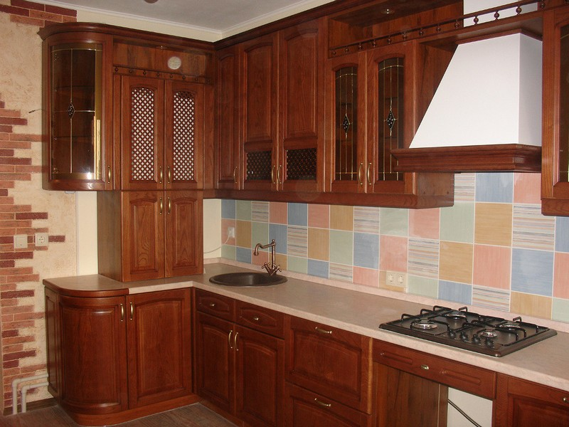 Wooden facades of the Classic designed kitchen and colorful tiled splashback