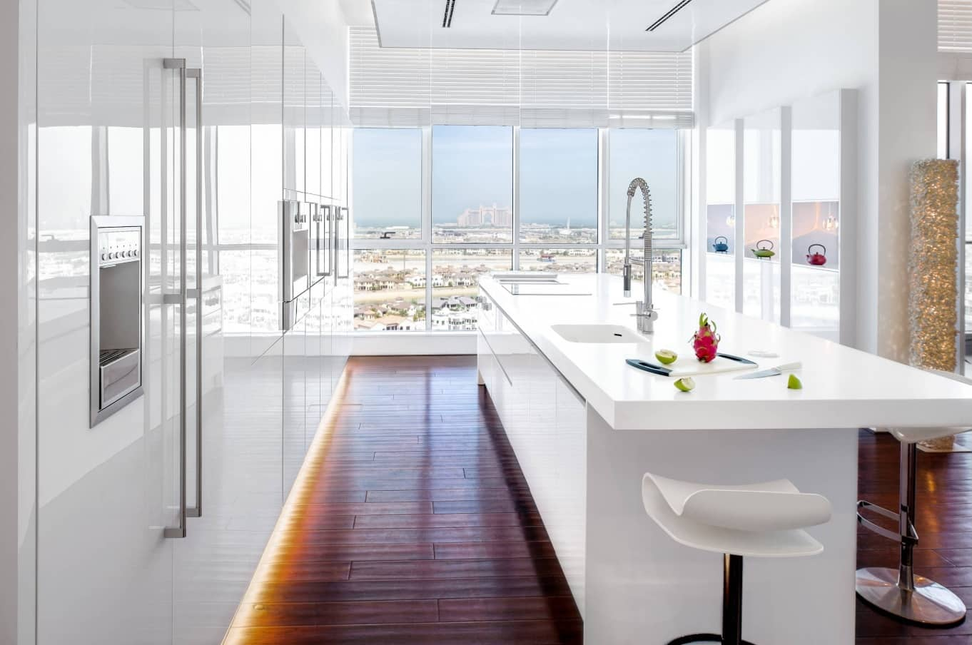 7 Home Collections by Luxury Fashion Brands. Ultramodern kitchen in the penthouse apartment with white glosy facades, backlight and dark wooden floor
