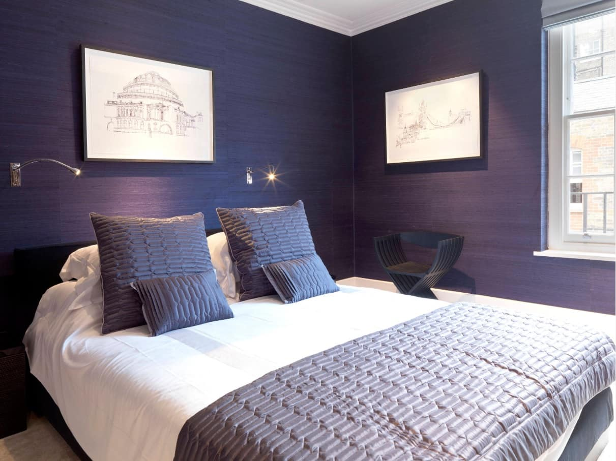 Purple walls in the bedroom with king-size bed