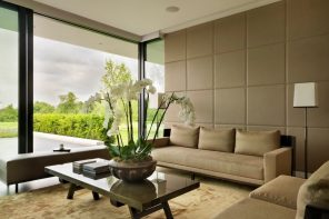 Utterly modern living room interior with panoramic windows and soft wall panels