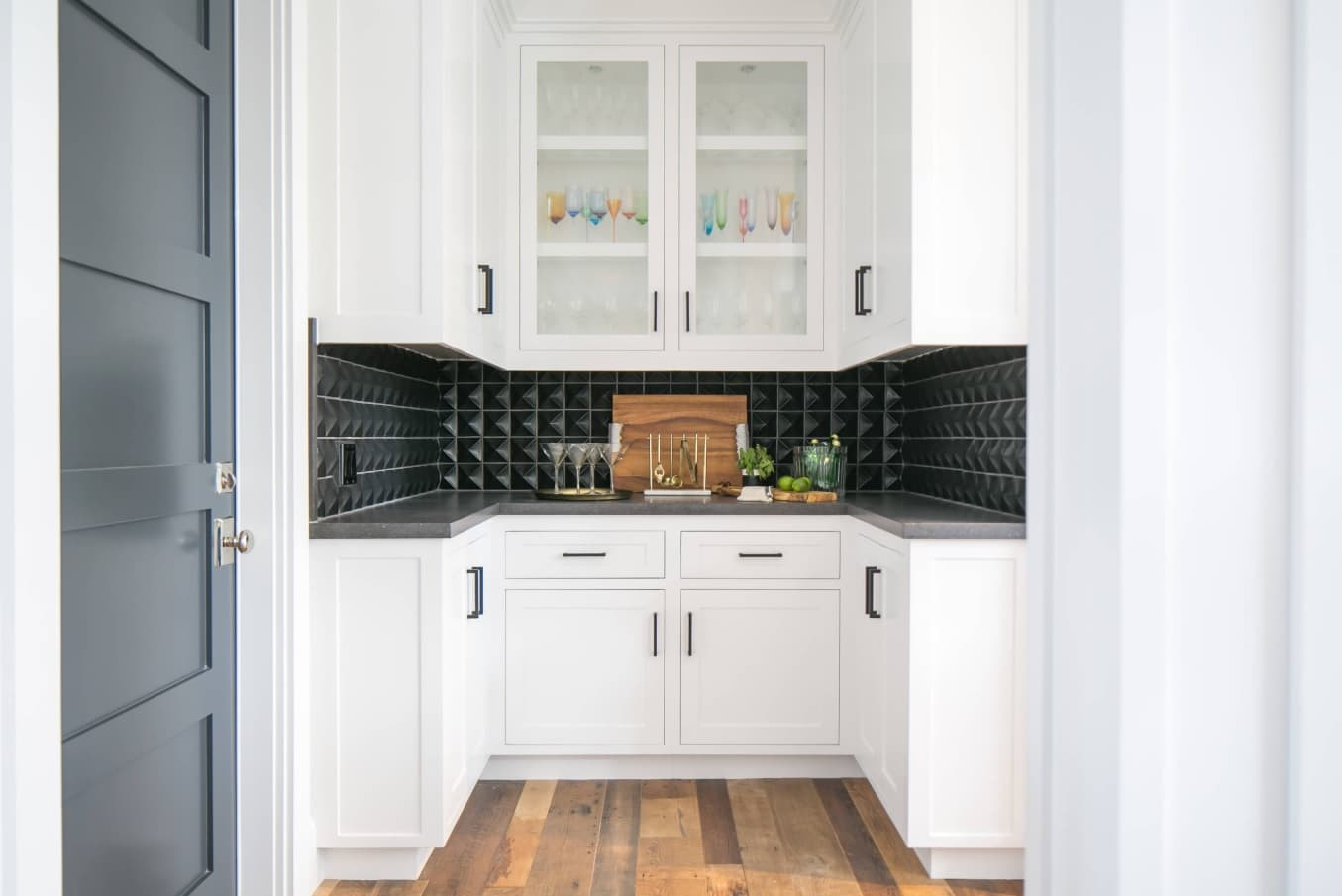 White kitchen furnniture facades and black splashback with voluminous tile