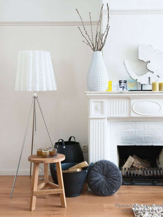 White vase and dofferent elements to adorn the mantelshelf of classic fireplace