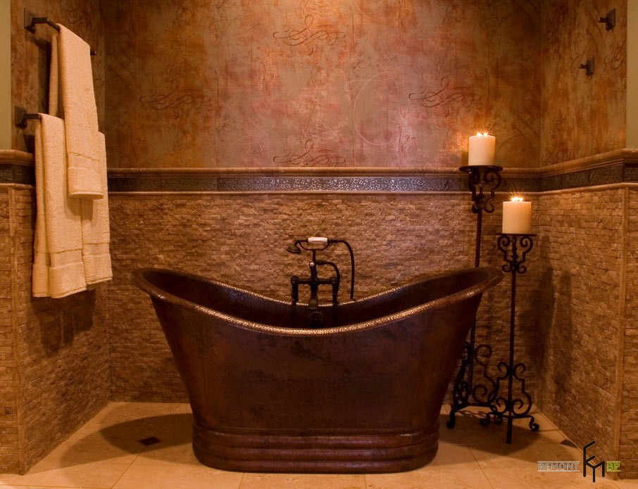 Candles and Candlesticks in the Modern Interior of Cozy Home. Brass bathtub for unusual Classic bathroom with reddish wall color
