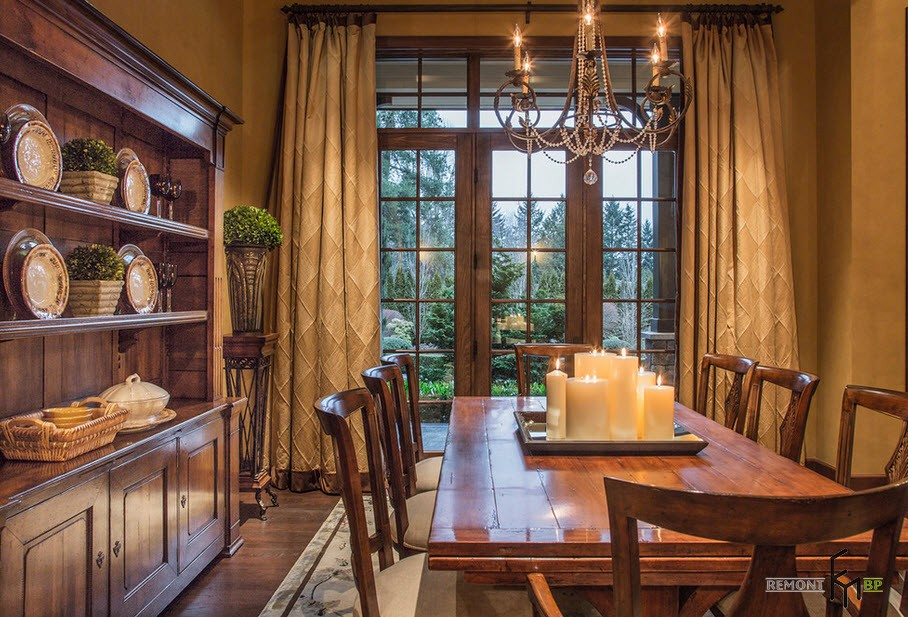 Long neutral ceurtains, wooden furniture and candles at the table of the Classic dining room